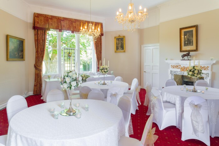 The Salisbury room set up for a reception with white table cloths on round tables, chairs in white covers with yellow bows