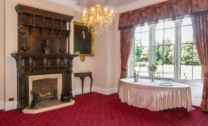The Mayor's parlour set up with a table in front of the window that looks out onto the main lawn, the ornate wooden fireplace in the centre of the roo