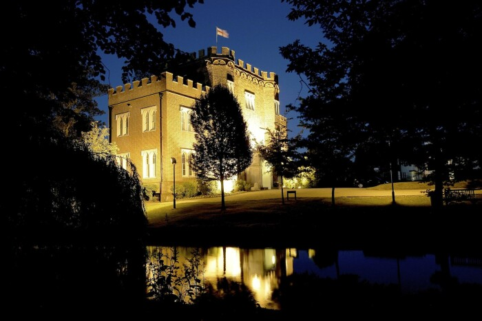A side view of Hertford Castle at night, light up by the uplighters, the trees silhouettes in the foreground