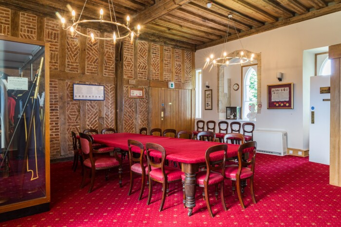 The robing room with a large red velvet covered table, the original brick and timber wall in full view