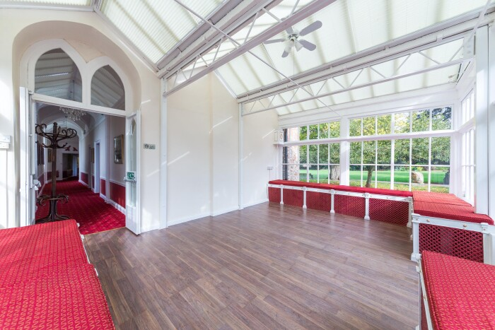The Conservatory with white metal frame and glass looking out over the main lawn, the red cushioned benches around the edges