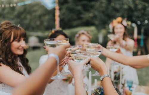 A bride and her bridal party holding champagne coupes and toasting together