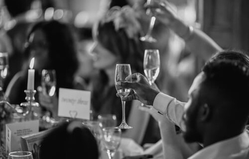 A black and white photo of guests toasting with champagne flutes