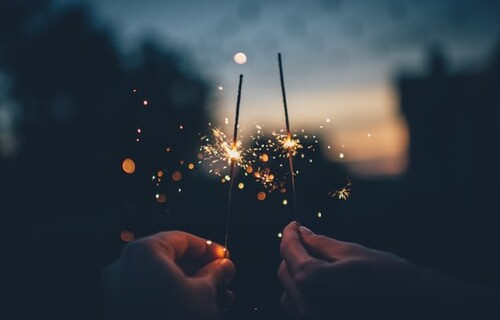 A close up of two sparklers alight in the night