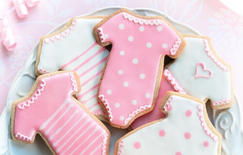 A close up of some decorated biscuits in the shape of baby playsuits, in pink and white with spots and stripes