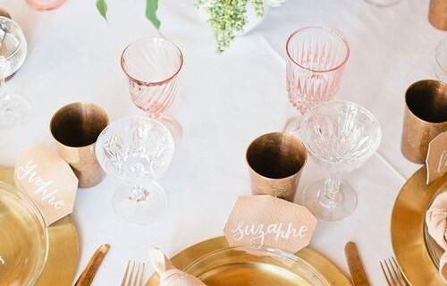 A close up of a table set for dinner, with gold plates, pink napkins and glasses and a floral arrangement as a centrepiece