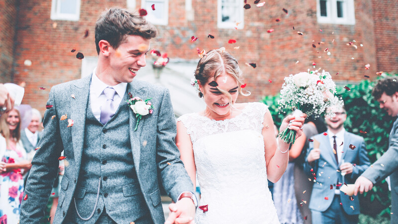 A bride and groom smiling, surrounded by friends and family throwing confetti