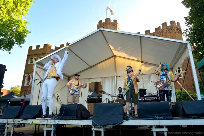 A man dressed all in white is on stage with his band, under a white canopy in front of hertford castle. It's a shot from the Rock at the Castle