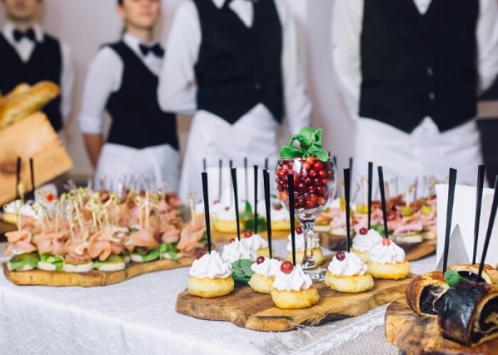 A close up of a table, with waiters in the background, covered in canapes and other food bits