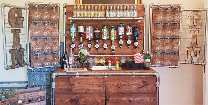 A wooden bar set up in a industrial style with glasses hanging on the side panel ans the words gin spelled out on the wings, bottles of of alcohol han