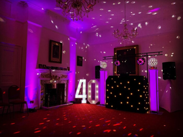 A DJ set up in the Salisbury room with disco balls and lighting, and a giant 40 in lights
