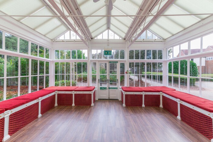 A wide shot of the conservatory, with its white frame, and red cushions on the benches around the edges.